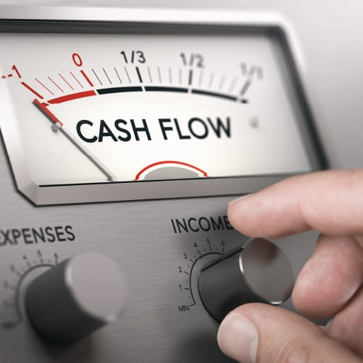 Business manager turning dials labeled expenses and income that control a meter labeled cash flow.